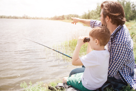 Boy is sitting with his dad at the river shore and looking through binoculars. Adult man is pointing forward and holding fishing rod in right hand. Stock Photo