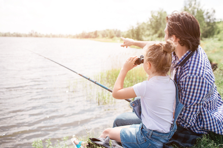 Man is sitting on grass near water with his daughter and pointing forward. Girl is looking there through binoculars. He is holding fishing rod in hands.
