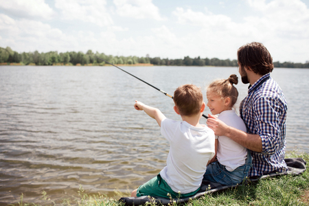 A picture of man and his children sitting together on the river shore. Guy is fishing while his kids are watching on it. Man is holding long fishing rod. Stock fotó