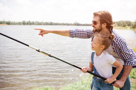 Adult man is pointing forward and showing it to his daughter. He wears glasses. Girl is standing with him and holding fishing rod. She is fishing. Stock Photo