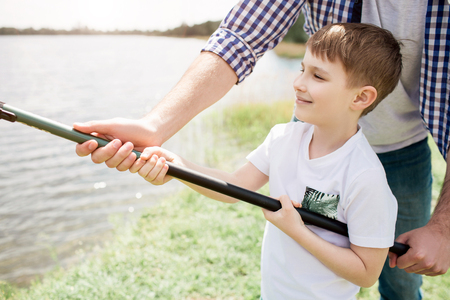 A picture of guy helping his son to hold fishing rod in a right way. He is holding it with one hand while boy is doing that with two hands. Small man seems like happy boy.