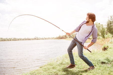 Calm and thoughtful guy is standing at the edge of lake and looking at it. He is holding fishing rod on his right shoulder with right hand. There is a beautiful weather outisde. Фото со стока - 103370872