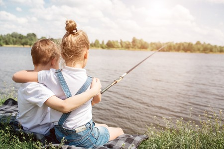 Gorgeous kids are sitting together near lake and hugging each other. Girl is fishing. She is holding fishing rod. They are alone there.