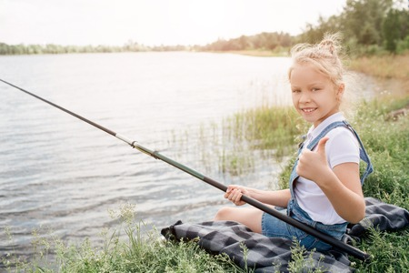 Girl is sitting on blanket alone and holding fishing rod in right hand. Also she is looking on camera and smiling. Girl is keeping her bit thumb up.