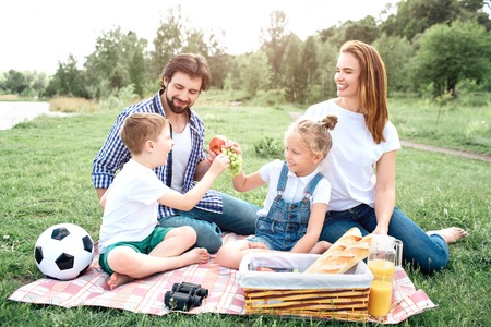 People from one family is sitting together and having fun. Kids are splitting grapes whiile man has an apple in hand. Woman is looking at it and laughing.