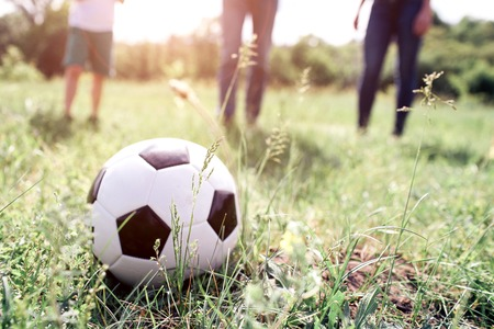 A picture of ball lying in grass. There are members of one family playing with it. They are ready to push ball. They are playing on meadow.
