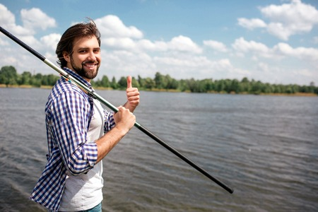 Happy guy is standing near river and looking on camera. He is smiling. Guy is holding fishing rod with right hand on right shoulder. Also man is pointing up. He looks happy.