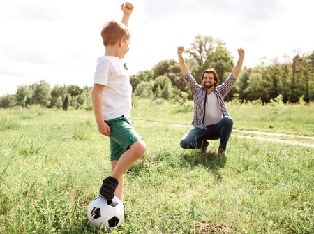 Father is screaming and yelling. He is very happy for his son. Boy played a good game. He won. Boy is standing besides his father and holding ball with leg. Stok Fotoğraf