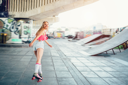 Blonde girl is rollerblading. She is looking back on camera. Her face is particulary covered with her hair. She is rollerblading very active.