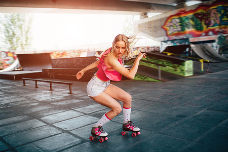 Beautiful blonde girl is doing some tricks during roller skating. She is standing in a squat position and looking down. Her hands are aside of body. She is exercising in training room. Foto de archivo - 103376548