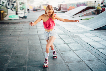 Well-built and slim girl is posing on camera. She is looking down to her knees and rollerblading. She is doing that very good.