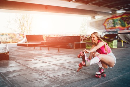 Una foto de una linda chica sentada en posición de cuclillas. Estira la pierna izquierda y trata de mantener el equilibrio. La muchacha sostiene la mano derecha en el borde del rodillo. Foto de archivo