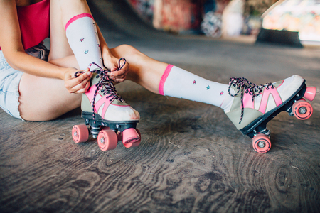 A picture of well-built and slim legs of one girl. She is sitting on concrete and tying laces on rollers. They are pink color. Girl is keeping left leg over right one. Banco de Imagens
