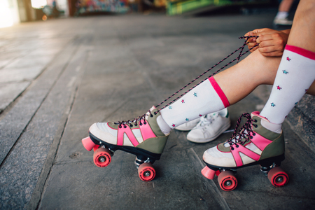 Girl is sitting on the floor and tying laces on her right roller. She is pulling them back. Also she put her right feet on the back rollers wheels. Stock Photo