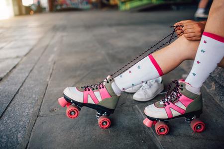 La fille est assise sur le sol et attache des lacets sur son rouleau droit. Elle les retire. Elle a également mis ses pieds droits sur les roues arrière des rouleaux.