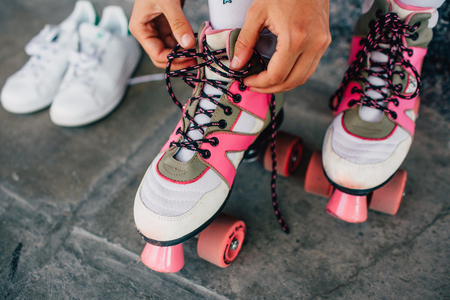 A picture of girl lying laces on her pink rollers. She has changed her white shoes to this funny rollers. Girl is almost ready to rollerblading. Banco de Imagens