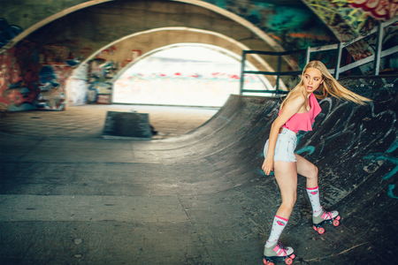Beautiful and well-built blonde girl is rollerblading in the special training room. She is going down backwards. Girl is looking behind with a serious sight. She is concentrated. Stock Photo