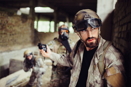 Handsome and bearded guy is leaning to wall and looking right. He is careful. Man has stopped his soldiers from attacking. They are waiting.