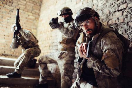 Drie krijgers staan op trappen en poseren. De man aan de voorkant kijkt recht vooruit en houdt een pistool vast. De tweede man richt ongecompliceerd. De derde man kijkt op met een geweer.