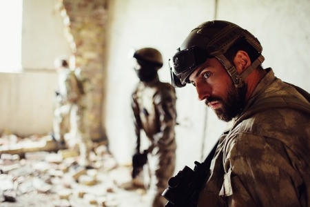 Bearded soldier is standing with his comrades in a ruined room. He is very concentrated. Guy is listening. Other warriors are standing further and closer to window.