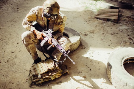 A picture of soldier sitting on the ground and wearing face mask. He is holding black rifle in hands. Man is looking odwn to bag. He has some rest. 写真素材