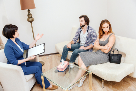Young couple is sitting together and looking to different sides. They have and argument. Psychologis is sitting in front of them and trying to help them. She is talking to them.