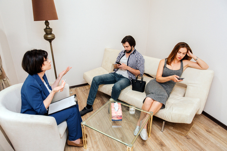 Adult couple is sitting and looking at their phones. They are bored. People dont listen to therapist. Doctor is trying to talk to them and showig that with her hands.