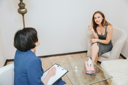 Good-looking and nice girl is sitting in front of therapist and listening to her very carefully. She is crossing her legs. Young woman is interested in having conversation with psychologist. Stok Fotoğraf - 103877722