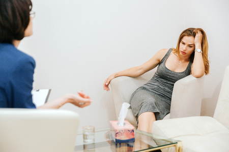 Tired girl is sitting on sofa and listening to therapist. She is in despair. Girl is looking down and holding her head with hand. Doctor is talking to her. Stockfoto - 103877793
