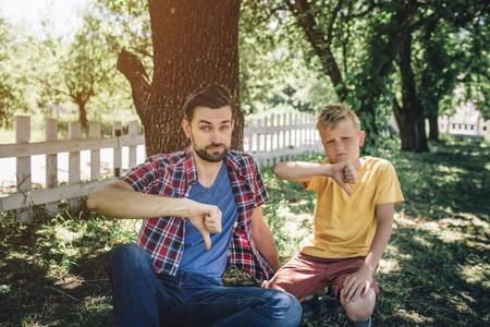 悲しくて動揺した人たちはひざまずいて大きな親指を押さえています。男の子は深刻な光景でカメラを見ています。彼らは公園に座っている。