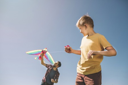 Nice picture of father and son playing with kite. Child is holding thread from it while dad is trying to run it to the sky. There is a blue background behind them.