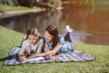 Happy mom is lying on blanket with her daughter. She holds her hand on piece of paper. Girl is drawing with yellow marker. They are smiling and looking down.