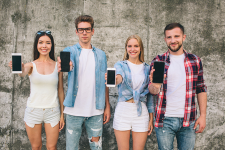 Nice and positive young people are standing on grey background and looking on camera. They are smiling. Girls and boys are holding phones in hands and showing it to camera. 写真素材