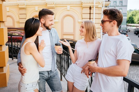 Nice girls and boys are standing couple by couple in front of each other. Blonde girl is talking to bearded guy. Bearded guy is embracing chinese girlfriend. He is holding a cup of coffee.