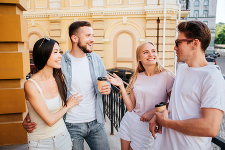 Nice friends are standing together in front of each other and talking. Bearded guy is holding a cup f coffee and embracing his chinese girlfriend. Blonde girl is looking at guy in glasses.