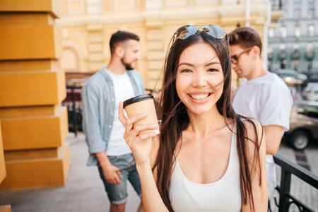 Portrait of happy chinese girl looking on camera and smiling. She is holding a cup of coffee in hands. There are two guys standing behind her. They are talking to each other.