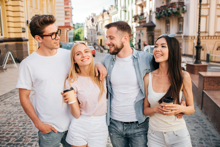 A picture of beautiful people standing together and posing. Blonde girl is smiling on camera and holding cup of coffee. Chinese girl is looking at guy in glasses. Bearded guy is looking at blonde girl.