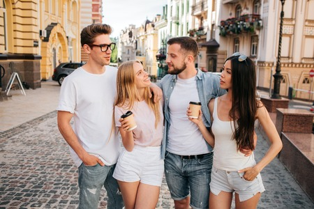Interesting picture of girls holding cups of coffee and looking a bearded guy. He is stnading with his eyes closed. Guy in glasses is looking at chinese girl. They are standing together and posing.