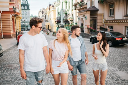 Two couples are walking on the street. Guy in glasses and blonde girl is walking in front. They are looking at each other and smiling. Another couple is walking behind.