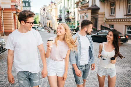 Young people are walking together down the street and talking to each pther. Blonde girls is holding cup of coffee in hands and looking at guy in glasses. Chinese giri is looking at bearded guy.