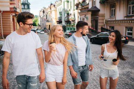 Cheerful young people are walking down the street. Three of them are looking at chinese girl. She holding glasses and cup of coffee in hands. All of them are smiling.