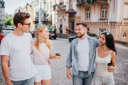 Two couples are walking down the street together. First couple is looking at the second one. Girls are holding cups of coffee in hands. They look satisfied and cheerful.