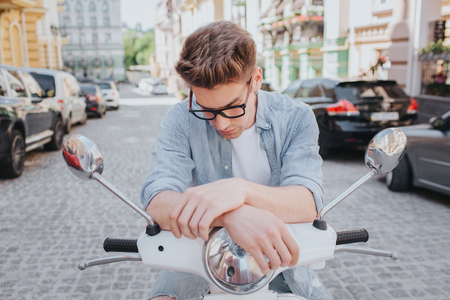 Handsome guy is sitting on motorcycle and looking down. He wears glasses