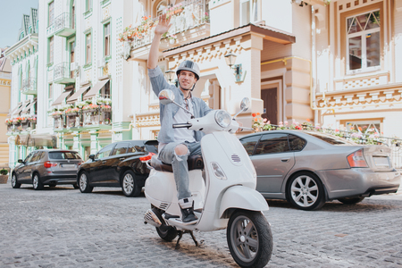 Man in casual clothes is riding on motorcycle. He is wearing helmet on head. Guy is holding fist in air and looking to the side. He is riding on road.