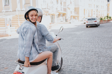 Attractive girl is posing on camera. She is looking back. Girl and her boyfriend wear helmets. He is driving the motorcycle.