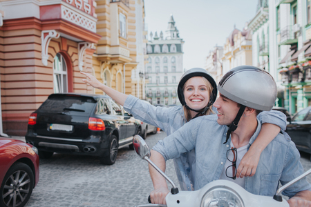 Happy girl is riding on bike with her boyfriend. They are looking straight forward. Guy is smiling. He is driving motorcycle. Girl is leaning to him.