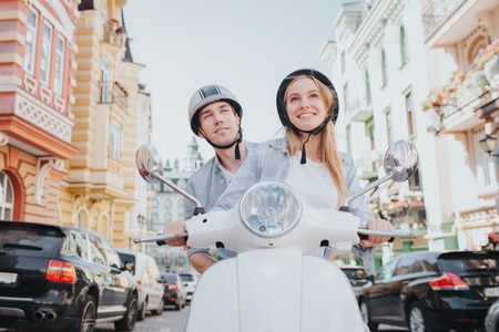 Attractive and positive girl is sitting in front of guy and looking forward. She is smiling. Guy is looking behind her back and looking forward too. They wear helmets. Standard-Bild - 104619177