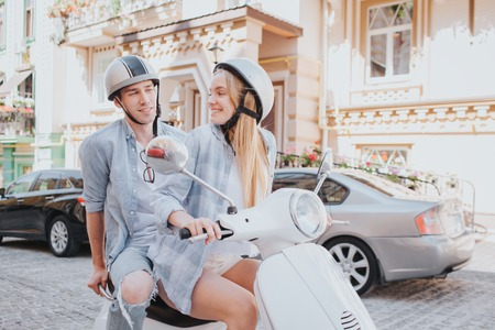 A picture of girl sitting on a front sit of motorcycle and looking back at her boyfriend. She is smiling to him. Guy is looking at her and holding his hands on the back of motorcycle.