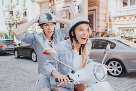 Excited girl is driving motorcycle. She is very happy about that. Guy is sitting behind her and looks frustrated. He is afraid of safety. Young man is holding hands on helmet.