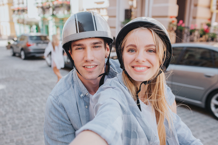 Beautiful couple is sitting on motorcycles seats and looking on camera. Girl is holding camera. She is taking selfie. They are smiling.